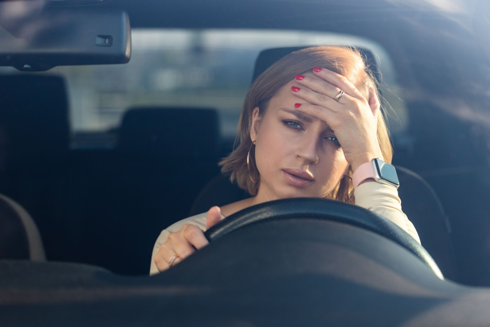 woman sitting her car looking frustrated as it vibrates while in idle position